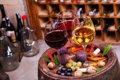 Het rood, nam en witte glazen en flessen wijn toe Druif, fig., noten en bladeren op oud houten vat Royalty-vrije Stock Fotografie