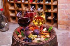 Het rood, nam en witte glazen en flessen wijn toe Druif, fig., noten en bladeren op oud houten vat Royalty-vrije Stock Foto