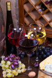 Het rood, nam en witte glazen en flessen wijn toe Druif, noten, kaas en oud houten vat Stock Foto's