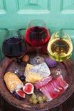 Het rood, nam en witte glazen en flessen wijn toe Kaas, fig., druif, prosciutto en brood op oud houten vat Stock Foto