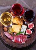 Het rood, nam en witte glazen en flessen wijn toe Kaas, fig., druif, prosciutto en brood op oud houten vat Mening van hierboven Royalty-vrije Stock Afbeeldingen