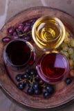 Het rood, nam en witte glazen met druif op oud houten vat toe Mening van hierboven, hoogste studioschot Stock Foto