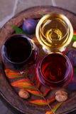 Het rood, nam en witte glazen wijn toe Druif, fig., noten en bladeren op oud houten vat Mening van hierboven, hoogste studioschot Royalty-vrije Stock Foto