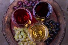 Het rood, nam en witte glazen wijn toe Druif, fig., noten en bladeren op oud houten vat Mening van hierboven, hoogste studioschot Stock Fotografie