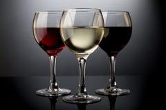 Het rood, nam en witte wijnglazen op een zwarte achtergrond toe Royalty-vrije Stock Fotografie