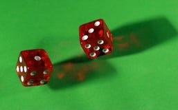 Het rood van Rolling dobbelt op groene lijst Stock Foto's