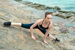 Het roodharige, jonge, atletische, mooie meisje nam in gymnastiek, looppas in openlucht in dienst Voert sportenoefeningen voor ui royalty-vrije stock afbeeldingen