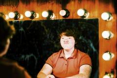 Het roodharige jongen stellen voor spiegel stock foto's