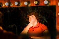 Het roodharige jongen stellen voor spiegel stock fotografie