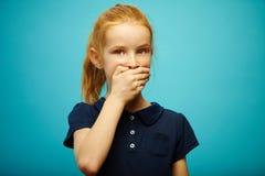 Het roodharige meisje behandelde haar mond met hand en bekijkt camera met zorg over geïsoleerde blauwe achtergrond, uitdrukt stock fotografie