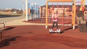 Het roodharige meisje berijdt op een zelf-in evenwicht brengt autoped Kinderen op de speelplaats stock videobeelden