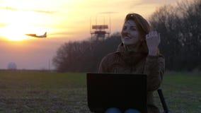 Het roodharige meisje gebruikt laptop dichtbij radar van luchthaven Vliegende vliegtuigachtergrond stock videobeelden