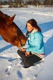 Het roodharige meisje op een sneeuwgebied voedt een appel van handen stock afbeeldingen