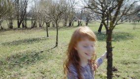 Het roodharige meisje speelt in een zonnig park stock footage