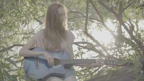 Het roodharige meisje spelen in een park op een gitaar, kleurenprofiel Slog3 stock videobeelden