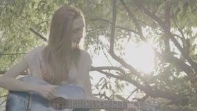 Het roodharige meisje spelen in een park op een gitaar, kleurenprofiel Slog3 stock video