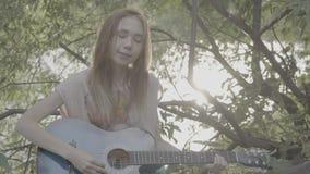 Het roodharige meisje spelen in een park op een gitaar, kleurenprofiel Slog3 stock footage