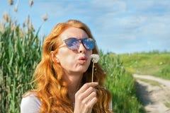 Het roodharige meisje in zonnebril blaast paardebloem weg Royalty-vrije Stock Afbeelding