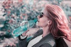 Het roodharige meisje in zonnebril met waterfles Royalty-vrije Stock Fotografie
