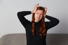 Het roodharigemeisje ervaart een vreselijke hoofdpijn migrain op een grijze achtergrond royalty-vrije stock afbeelding