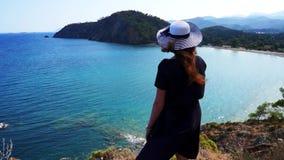 Het roodharigemeisje kijkt van een heuvel op de Middellandse Zee in Phaselis Stad van oude Lycia Turkije stock footage