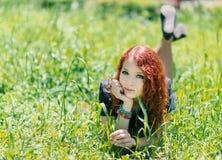 Het roodharigemeisje legt op gras stock afbeeldingen