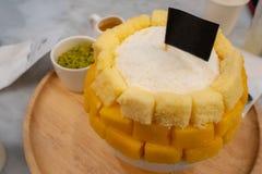 Het roomijs Koreaans dessert van mangobingsu in kom op houten dienblad op lijst royalty-vrije stock afbeeldingen
