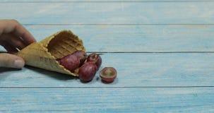 Het roomijs van de bes Bessen van druif in een wafel op een blauwe houten achtergrond stock video