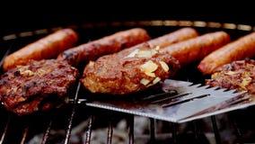 Het roosteren: burgers en hotdogs op houtskoolbrand stock footage