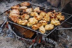 Het roosteren van barbecuekip over kampvuursteenkolen stock fotografie