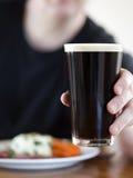Het roosteren van de mens met een bier Stock Afbeelding