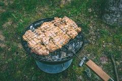Het roosteren van heerlijke verscheidenheid van vlees bij de grill van de barbecuehoutskool G stock foto