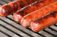 Het roosteren van hotdogs Stock Afbeeldingen