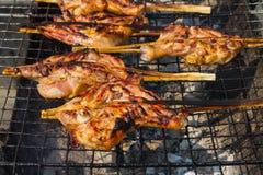 Het roosteren van kip bij de houtskoolgrill Stock Foto's