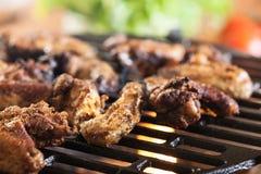 Het roosteren van kippenvleugels bij de barbecuegrill Stock Afbeelding
