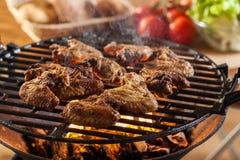 Het roosteren van kippenvleugels bij de barbecuegrill Royalty-vrije Stock Foto's