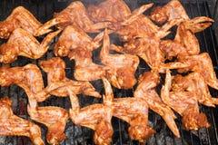 Het roosteren van kruidige kippenvleugels bij de barbecuegrill stock foto's