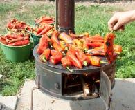 Het roosteren van rode paprika voor de winterbepalingen Stock Afbeelding