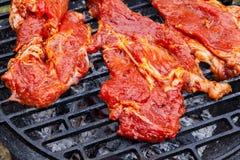 Het roosteren van ruwe varkensvleeslapjes vlees bij de barbecuegrill Royalty-vrije Stock Afbeeldingen