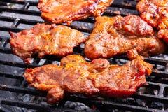 Het roosteren van varkensvleeslapjes vlees bij de barbecuegrill Stock Foto