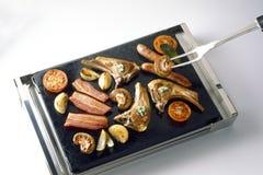 Het roosteren van voedsel op een kokende steen Stock Fotografie