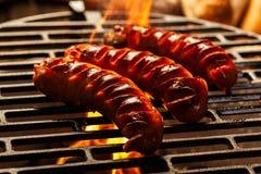 Het roosteren van worsten bij de barbecuegrill Royalty-vrije Stock Foto's