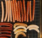 Het roosteren van worsten bij de barbecuegrill Stock Fotografie