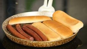 Het roosteren van worsten en brood op een pan terwijl het koken van eigengemaakte hotdogs stock footage