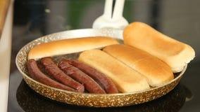 Het roosteren van worsten en brood op een pan terwijl het koken van eigengemaakte hotdogs stock video