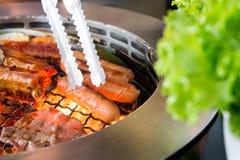 Het roosteren van worsten en vleesbarbecue op een grill Koreaanse stijl Stock Fotografie