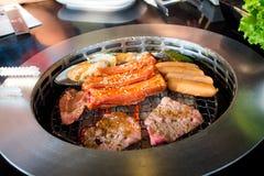 Het roosteren van worsten en vleesbarbecue op een grill Koreaanse stijl Royalty-vrije Stock Foto's