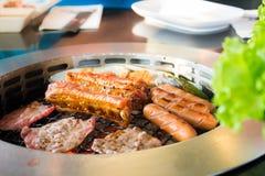Het roosteren van worsten en vleesbarbecue op een grill Koreaanse stijl van de kant Royalty-vrije Stock Fotografie
