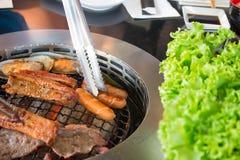 Het roosteren van worsten en vleesbarbecue op een grill Koreaanse stijl met tong die aan bestelwagenworst proberen Stock Foto
