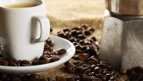 Het roteren dolly schot van koffiezetapparaat aan kop van espresso met koffiebonen op de stof van de jutezak stock videobeelden